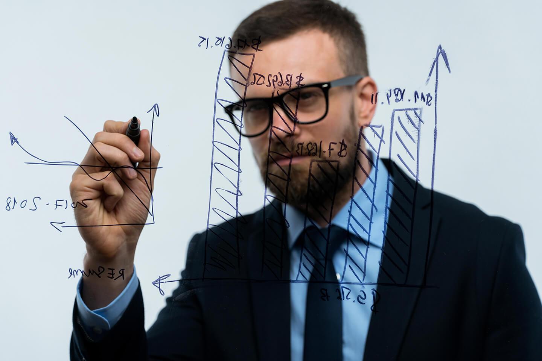 man draws various growth charts calculating - بررسی ریسک و میزان سود ساخت یک کارخانه